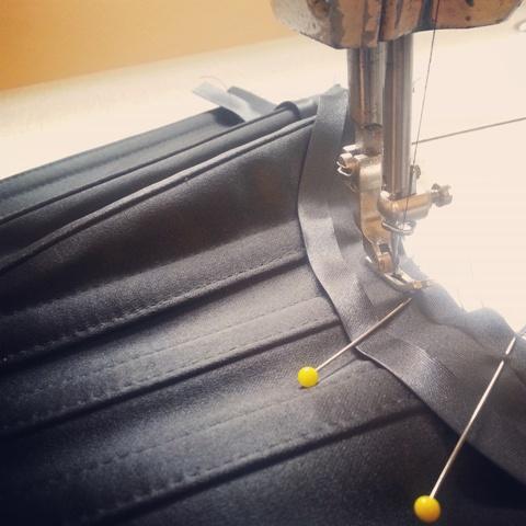 Machine stitching bias binding on a bespoke corset.