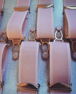 A close up of pink suspenders with gold fittings