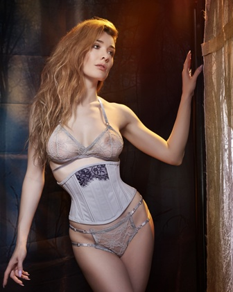 Model wears a grey coutil waspie with lace detail.