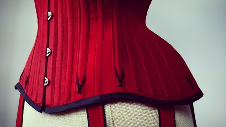 Flossing on a scarlet silk satin corset