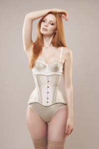 Model wearing an ivory and pale gold silk Edwardian underbust corset embellished with lace.