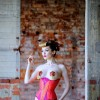Miss Miranda wears orange and cerise silk training corset