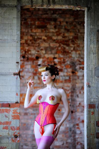 Miss Miranda wears orange and cerise silk training corset