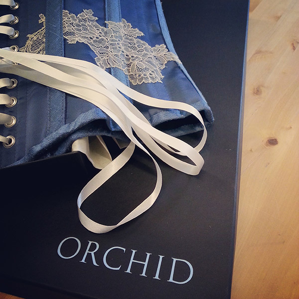 A close up of Orchid branded boxes, with a bridal corset resting on top.