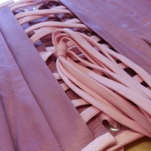 A close up showing covered eyelets on a pink corset