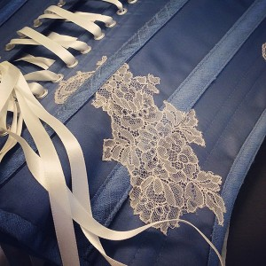 Detail from a Wedgwood blue satin corset with cream lace over and under-lapping boning accents