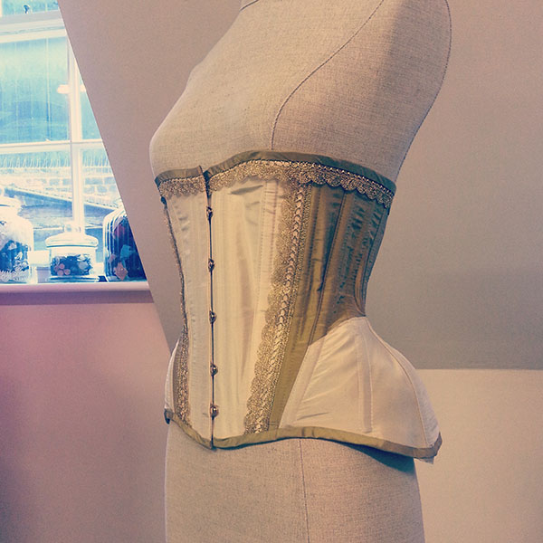 An ivory and gold silk Edwardian underbust corset.