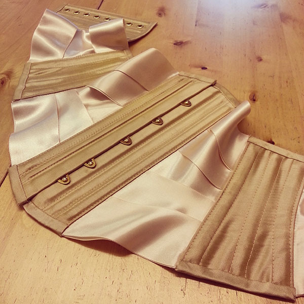 A ribbon corset made in gold silk.