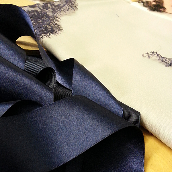 A selection of navy ribbons and lace laid out for perusal.
