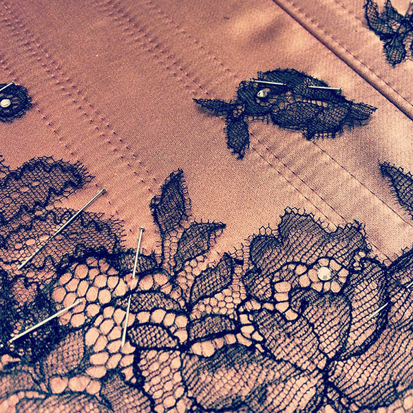 Black chantilly lace applique on a dusky rose satin.
