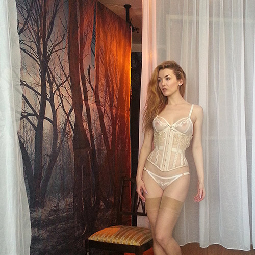Model wearing ivory sheer corset and lingerie.