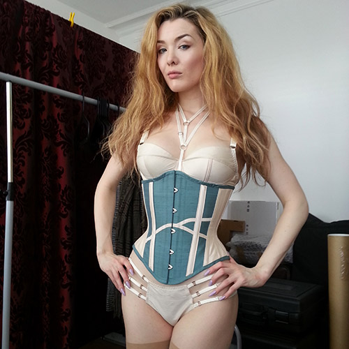 Model wearing a marine and ivory silk underbust corset with ivory silk lingerie.