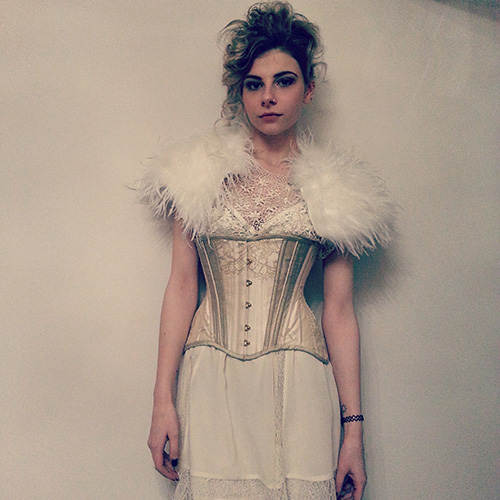 Model wearing ivory corset and feather stole.