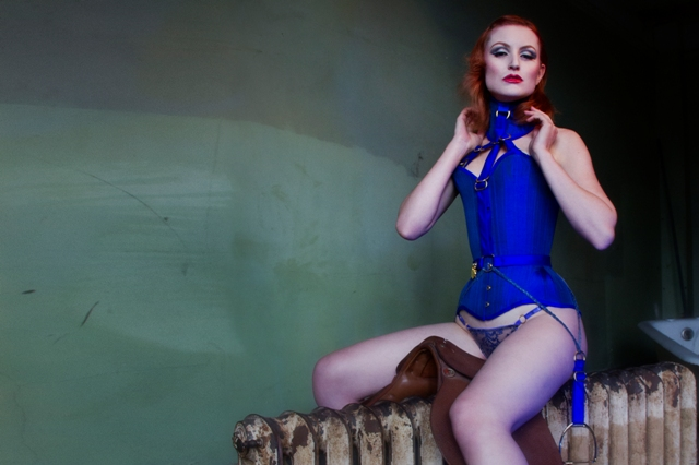 Model wears blue silk overbust corset and posture collar