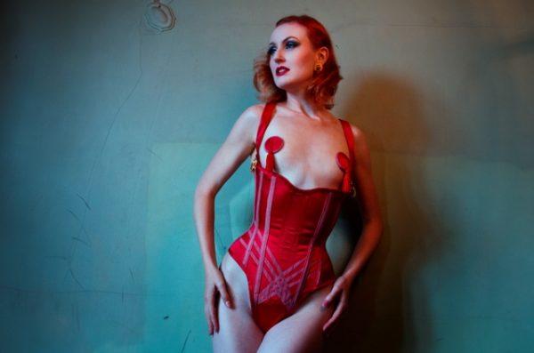 Model wearing a red silk corset body