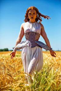 Model wears a corset with wings in a cornfield
