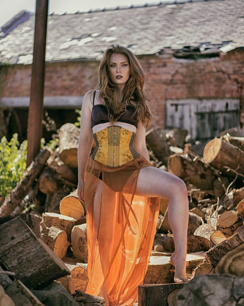 Model wears corset and flowing skirt on a wood pile