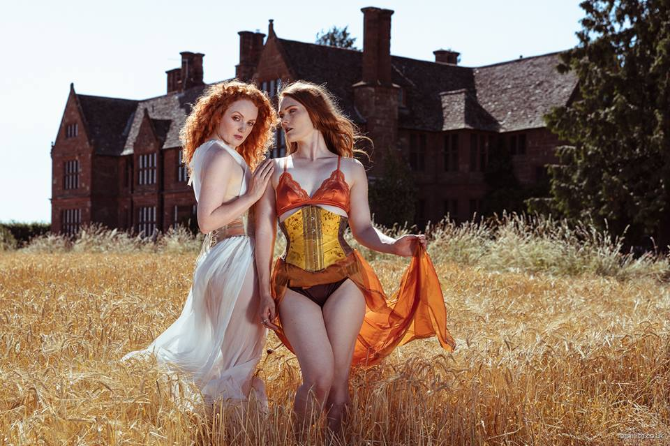 Two models wear corsets in a corn field.