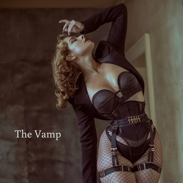 Model wears black mesh waspie with suspender belt